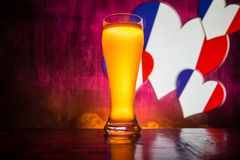 Creative concept. Pint of fresh beer on table with blurred flag of France on background or Glass of lager beer ready for drink. Co. Py space. Selective focus royalty free stock photos