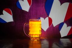Creative concept. Pint of fresh beer on table with blurred flag of France on background or Glass of lager beer ready for drink. Co. Py space. Selective focus stock photography