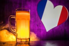 Creative concept. Pint of fresh beer on table with blurred flag of France on background or Glass of lager beer ready for drink. Co. Py space. Selective focus royalty free stock photo