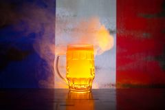 Creative concept. Pint of fresh beer on table with blurred flag of France on background or Glass of lager beer ready for drink. Co. Py space. Selective focus stock photo