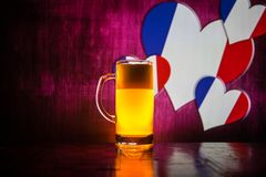 Creative concept. Pint of fresh beer on table with blurred flag of France on background or Glass of lager beer ready for drink. Co. Py space. Selective focus stock photos