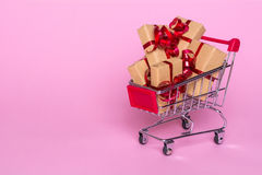 Creative concept with shopping trolley with gifts on a pink background. Gifts wrapped in kraft paper with a red ribbon and bow Stock Images