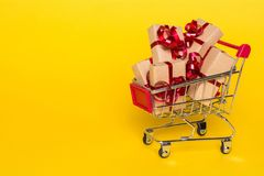 Creative concept with shopping trolley with gifts on a yellow background. Gifts wrapped in kraft paper with a red ribbon and bow Royalty Free Stock Photo