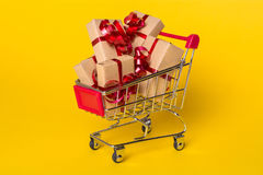 Creative concept with shopping trolley with gifts on a yellow background. Stock Photography