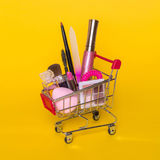 Creative concept with shopping trolley with makeup on a yellow background. Perfume, sponge, brush, mascara, pencil, nail file, eye shadow, lip gloss in the Stock Images