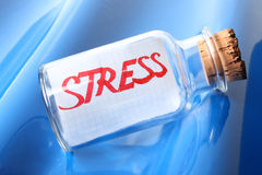 An artistic symbolic concept of a bottle with a message stress. Creative concept of a vintage bottle with a message stress on blue Stock Photography