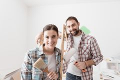 Creative couple renovating their house. Creative young couple renovating their house and painting walls, they are posing together and smiling at camera Royalty Free Stock Photo
