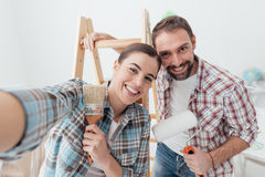 Creative couple renovating their house. Creative young couple renovating their house and painting walls, they are taking a self portrait together and smiling at Stock Photo
