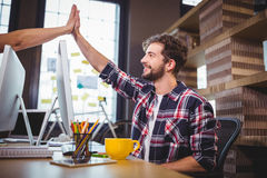 Creative coworkers high fiving at desk in office Stock Image
