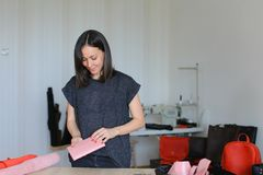 Creative woman making pink leather wallet at home atelier. Creative craftswoman making pink leather wallet at home atelier. Concept of home handicraft business Royalty Free Stock Photography
