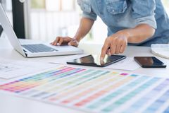 Creative creativity graphic designer working with graphics table. T,laptop and smart phone, colour chart at workplace on wooden desk , colour ideas style concept royalty free stock images