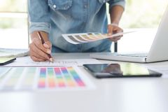 Creative creativity graphic designer working with graphics table. T,laptop and smart phone, colour chart at workplace on wooden desk , colour ideas style concept royalty free stock image