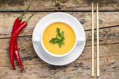 Creative cuisine. Pea Soup with chopstick on wood background Royalty Free Stock Photo