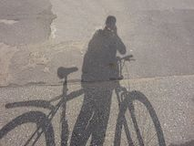 Creative Cycle Bicycle Cyclist Shadow Silhouette On The Asphalt Road. Surface stock images