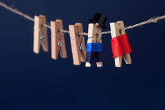 Creative design clothespin characters man in suit, woman red dress hanging on rope. concept with clothesline and dark. Creative design clothespin characters man Stock Images