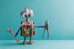 Creative design electrician robot with hand wrench pliers. Funny toy mechanic character lamp bulb eyes head, electric Royalty Free Stock Photography