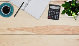 Creative design mockup set of workspace desk. Top view of home desktop. Calculator, mug with coffee or tea, pot with flower, noteb. Ook and pen laying on wooden Stock Image