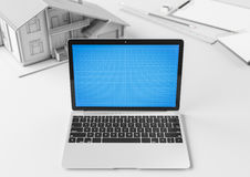 Creative designer and architect desktop with laptop, building model and stationery items. Mock up. Royalty Free Stock Images