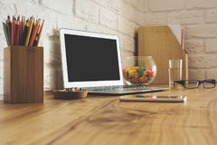 Creative designer desk top with empty laptop stock images