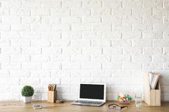 Creative designer desktop with empty laptop. Close up of creative designer desktop with empty laptop, supplies and other items. Technology and device concept Royalty Free Stock Photos
