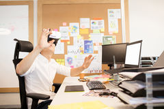Creative designer gesturing while experiencing vr glasses. In office Stock Images