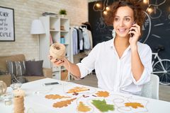 Creative Designer Speaking by Phone. Portrait of happy young woman speaking by phone while making handmade Autumn leaves decoration in modern apartment Stock Image