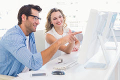 Creative designer talking to his colleague sitting at the desk Stock Photos