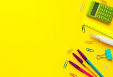 Creative desk with colourful stationery. Colored paper clip.School supplies on yellow background.Office desk. Back to school concept with space for text. Top royalty free stock photo
