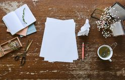 Creative desk pictures flowers cup of tea and sheets of paper royalty free stock image