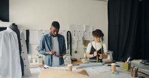 Creative dressmakers designing clothing using tablet and measure-tape in studio. Creative dressmakers beautiful Caucasian girl and African American guy are stock footage