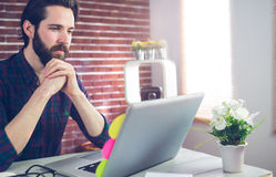 Creative editor with hand clasped using laptop. Confident creative editor with hand clasped using laptopp in office royalty free stock images