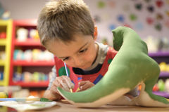 Creative education. Child painting a ceramic pottery model dinosaur at school concept for art and creative education Stock Photo