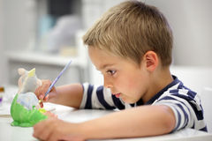 Creative education. Child painting a ceramic pottery model at school concept for art and creative education Stock Image