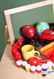 Creative education concept. Colorful school accessories. (apple, books, ball, headphones, tablet pc, cup) on table in classroom Stock Image