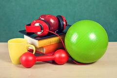 Creative education concept. Colorful school accessories in classroom. Creative education concept. Colorful school accessories (apple, books, ball, headphones Stock Images