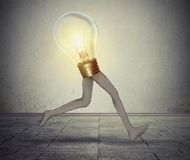 Creative energy quick thinking business concept. Glowing bright light bulb with long legs running fast creativity performance metaphor for fast production idea Stock Photo