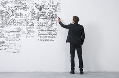 Creative entrepreneur sketching ideas. Elegant businessman rear view sketching with a black marker on a white wall Royalty Free Stock Photography