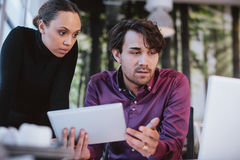 Creative executives searching information on internet. Two young business professionals working together on a project. Creative executives using digital tablet royalty free stock photos