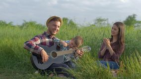 Creative family, happy laughing dad teaches son to plays stringed instrument while while mum claps and laughs while. Relaxing on picnic in nature in green field stock video