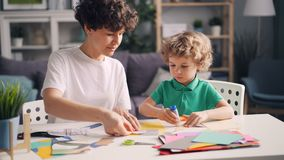 Creative family mom and small child doing collages with paper, scissors and glue. Creative family mom and small child are doing collages with colored paper stock video