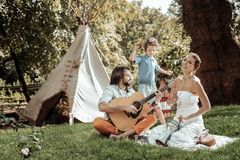 Creative family playing musical instruments near tent