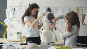 Creative fashion designers are pinning cut out pieces of fabric to mannequin while sewing women`s garment in modern. Light studio. Ladies are concentrated on stock footage