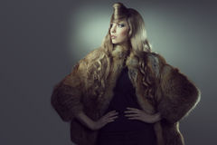 Creative fashion portrait of blonde girl. Portrait of fashion blonde girl posing with creative blonde hair-style and elegant warm fur coat. Winter style royalty free stock photo