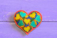 Creative felt heart for Valentines Day. Embroidered heart gift  on purple wooden background with copy space for text Stock Image