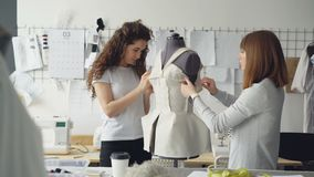 Creative female clothing designers are pinning cut out pieces of fabric to dummy while tailoring women`s garment in. Creative female clothing designers are stock footage