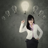 Creative female manager pointing at lightbulb Royalty Free Stock Photography