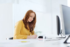 Creative female office worker writing to notebook Royalty Free Stock Photo