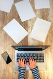Creative female person working on laptop computer in the office. Top view of hands typing keyboard on desk with smartphone and papers scattered around Stock Photography
