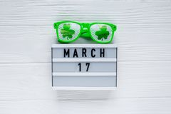 Creative festive St Patricks background with white light box calendar 17 march and fun green glasses with shamrock stock photography