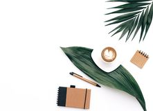 Creative flat lay background for blogger, keyboard, coffee cup and headphones. With green leaves. Minimal workspace royalty free stock photography